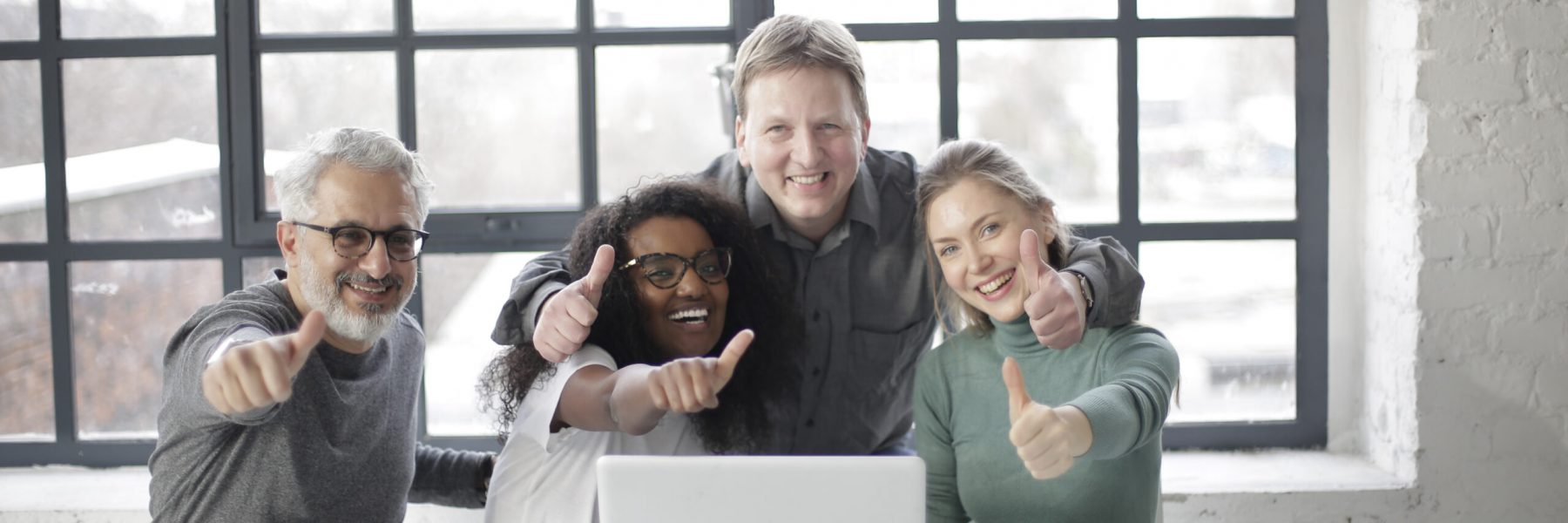 smiling-colleagues-with-laptop-and-thumbs-up-working-in-3931870